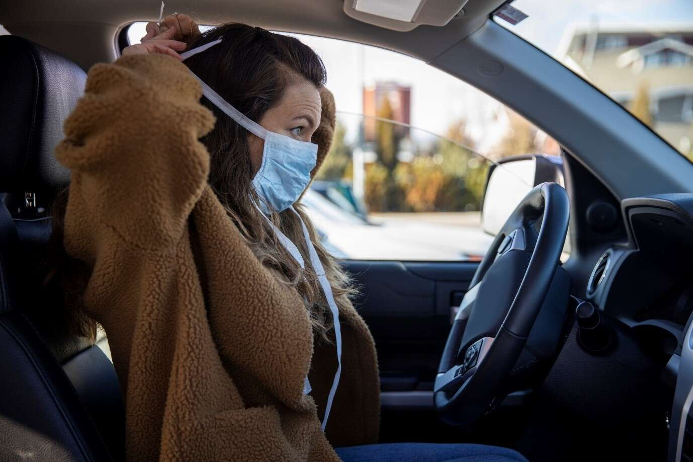woman putting mask on in car